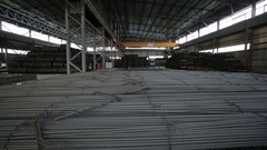 Warehouse full of tied reinforcing steel bars right to left wide shot Stock Footage