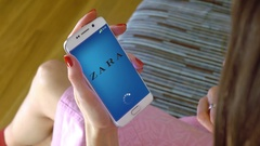 Young woman holding a cell phone with loading Zara mobile app. Conceptual Stock Footage