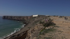 4k Tourists watching rough coastline cliffs and ocean beach at Sagres Portugal Stock Footage