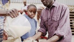 4K Family from poor African community work together measuring rice or grain Stock Footage