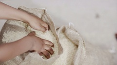 4K Hands of little boy from poor African community with hands in sack of rice Stock Footage