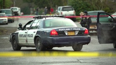 Police car parked in the street blocking it off with crime scene tape Stock Footage