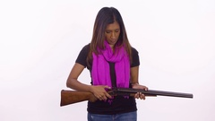 A woman checks her shotgun to see if it's loaded. It is. Medium shot on white Stock Footage