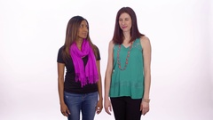 An interracial lesbian couple look at each other, smile and holds hands. Wide Stock Footage