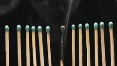 SLOW MOTION: Smoke of single burned matchstick between row of new matchsticks Stock Footage