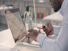 Man typing on laptop and using phone in a startup office - track left. Stock Footage