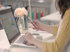 Woman typing on laptop and using phone in a startup office - track left. Stock Footage