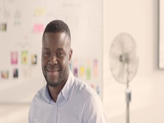 Moving portrait of a man in a startup office - track left. Stock Footage