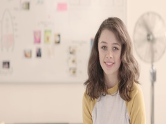 Moving portrait of a young woman in a startup office - track left. Stock Footage