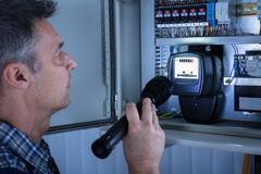 Electrician Examining A Fusebox Stock Photos