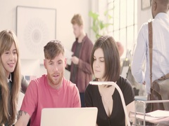 Young adults talking around desk in busy startup office track left by glass wall Stock Footage