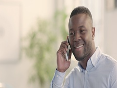 Portrait of happy man in bright startup office using mobile phone track left Stock Footage
